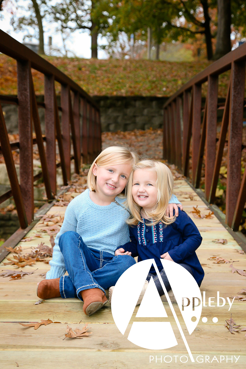 on location in fall sisters together on bridge with leaves